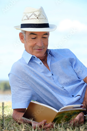 senior reading a book in the park