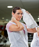 Woman Wiping Sweat With Towel At Health Club