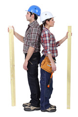 male and female carpenters standing back to back