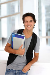 Cheerful college student standing in hall