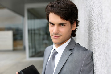 Closeup of young businessman leaning on wall