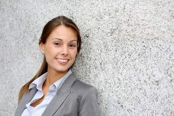 Smiling executive woman leaning on grey wall