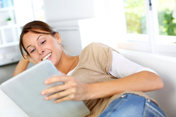 young woman using electronic tablet laying on sofa