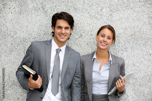 Cheerful business people standing on grey background