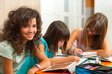 Portrait of teenage girl with friends doing homework.