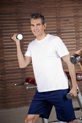 Happy Mature Man Lifting Dumbbells