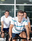 People On Spinning Bike In Health Club