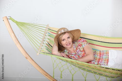 woman in a straw hat lounging on a striped hammock
