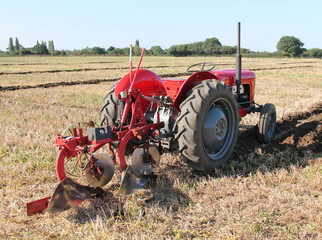 A Vintage Tractor and Plough Working on a Field.