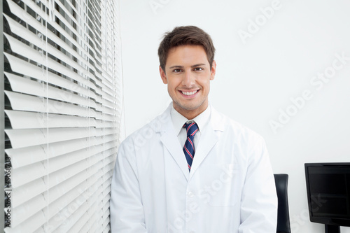 Happy Dentist Standing In Clinic