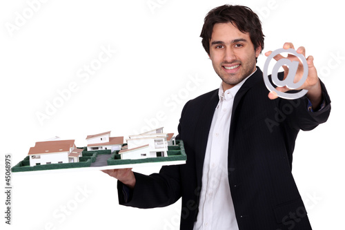 Architect with a model of a housing estate and an @ sign