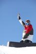 A snowboarder waving his arm