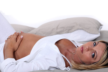 Pregnant woman laid on a bed