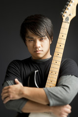 """""""Young man holding guitar, portrait"""""""