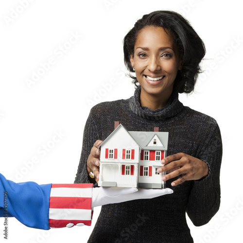 """Mid adult woman holding model house, studio shot"""