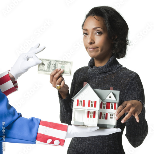 """Mid adult woman holding model house and paying for it, studio shot"""