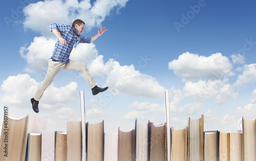 Man jumping over books