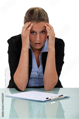 Shocked employee sitting at her desk