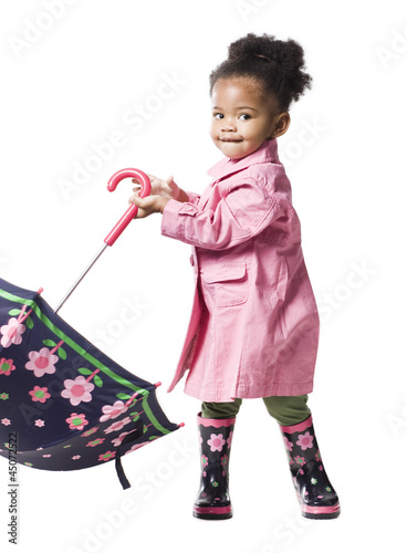 Studio portrait of baby girl (18-23 months) holding umbrella