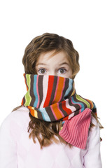 Studio portrait of girl (6-7) with scarf covering face