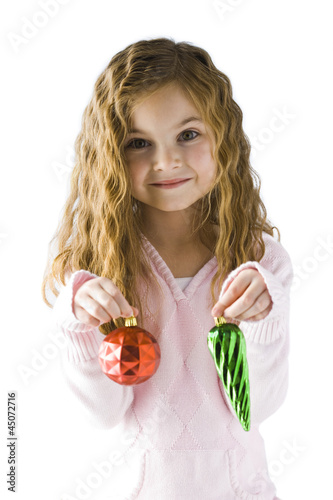Studio portrait of girl (6-7) holding Christmas ornaments