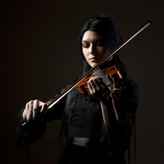 """Young woman playing violin, studio shot"""