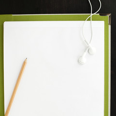 Pencil and earphones on blank paper with file