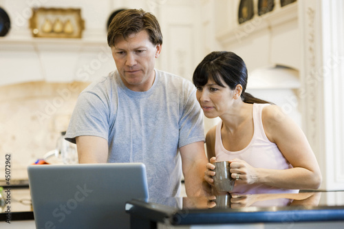 """USA, Utah, couple using laptop in kitchen"""