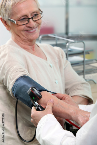 a nurse taking blood pressure of a smiling senior woman