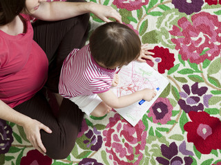 """USA, California, San Francisco, pregnant mother with daughter (2-3) coloring"""
