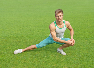 Young man exercising on green field