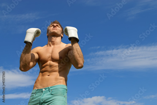 Strong man in boxing gloves. The winner.