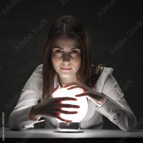 Studio portrait of young woman holding crystal ball
