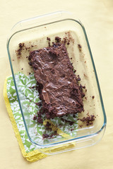 Half eaten chocolate cake in serving dish