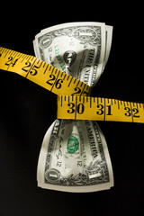 One dollar banknotes tied up with measuring tape against black background