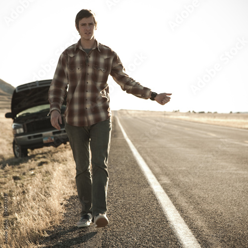 """USA, Utah, man hailing on road, broken car in background"""
