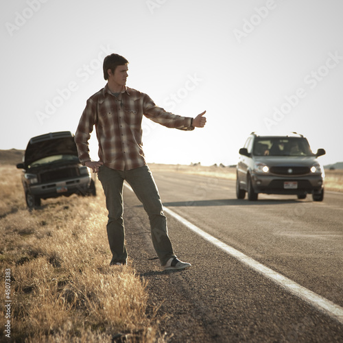 """USA, Utah, man hailing on roadside, broken car in background"""