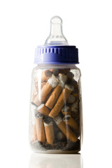 Cigarettes in baby bottle on white background