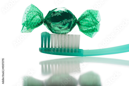 Candy with toothbrush on white background