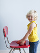 """Girl (2-3) putting whoopie cushion on chair, smiling, studio shot"""
