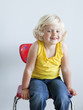 """Girl (2-3) girl sitting on chair, smiling, portrait, studio shot"""