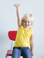 """Girl (2-3) girl sitting on chair and raising hand, studio shot"""