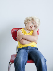 """Upset girl (2-3) sitting on chair, studio shot"""