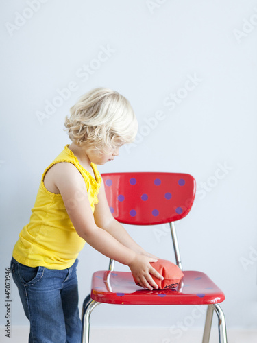 """Girl (2-3) putting whoopie cushion on chair, studio shot"""