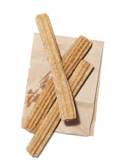 """Fresh churros on paper bag, view from above, studio shot"""