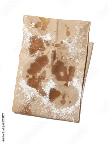 """Empty paper bag stained with oil and powdered sugar, view from above, studio shot"""