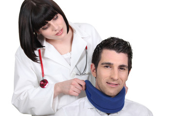Female doctor applying a neck brace to a male patient