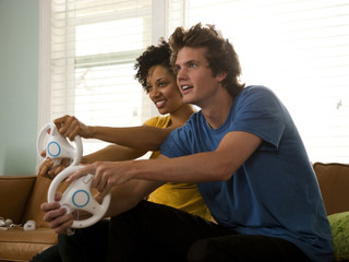 """USA, Utah, Provo, young couple playing video games in living room"""