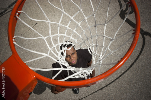"""USA, Utah, Salt Lake City, young man looking up at basketball hoop"""