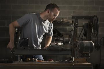 """USA, Utah, Orem, man using machine in workshop"""